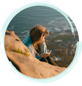 Lady Looking at Phone By A Beach | Fort Myers Addiction Therapy & Fort Lauderdale Addiction Therapy Services by A Peaceful Mind Counseling Group