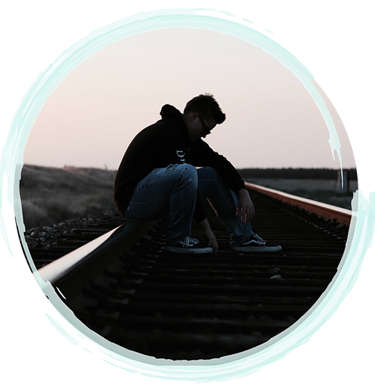 Image of a young man sitting on railroad tracks | Fort Myers Addictions Therapy & Fort Lauderdale Addiction Therapy Services by A Peaceful Mind Counseling Group | Addiction Counselors and Therapists in Fort Myers | Addiction Counselors and Therapists in Fort Lauderdale